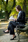 Businesswoman outdoor reading newspaper — Stok fotoğraf