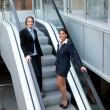 Two attractive businesswomen on escalator — Stock Photo