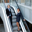 Two attractive businesswomen on escalator - Stock Photo