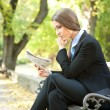 Thinking businesswoman reading newspaper — Stock Photo