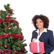 Woman with gift near christmas tree — Stock Photo #7801203