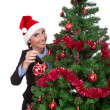 Royalty-Free Stock Photo: Woman  putting christmas ball on  christmas tree