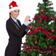 Royalty-Free Stock Photo: Young woman decorate a christmas tree