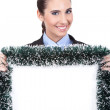 Smiling businesswoman holding christmas billboard — Stock fotografie