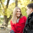 Smiling young couple talking in park - Stockfoto