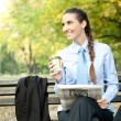Stock Photo: Young businesswomwith coffee and newspaper