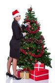 Woman arranging christmas tree — Stock Photo