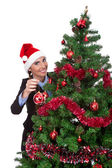 Woman putting christmas ball on christmas tree — Stock Photo
