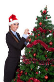 Young woman decorate a christmas tree — Stock Photo