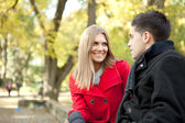 Smiling young couple talking in park — Stock Photo