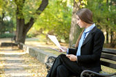 Businesswoman reading document, outdoor — Stock Photo