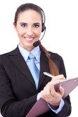 Businesswoman with headset making note — Stock Photo