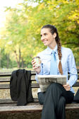 Young businesswoman with coffee and newspaper — Stock Photo