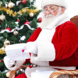 Santa Claus reading children gift letters for Christmas — Stock Photo
