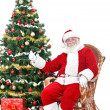 Stock Photo: Santa sitting next Christmas tree