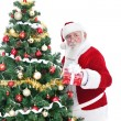 Santa next Christmas tree with gift — Stock Photo
