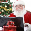Santa Claus working on laptop — Stock Photo
