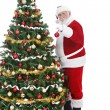 Santa Claus decorating Christmas tree — Stock Photo