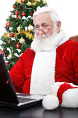 Modern Santa using laptop — Stok fotoğraf