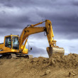 Stock Photo: Yellow excavator on hill