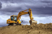 Yellow excavator on a hill — Stock Photo