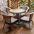 Stock Photo: Wicker chairs and table on hardwood front deck