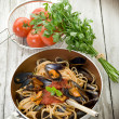 Spaghetti with mussels and tomato sauce over casserole - Stock Photo