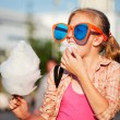 Girl eating cotton candy — Stockfoto