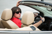 Young man driving a convertible car — Stock Photo