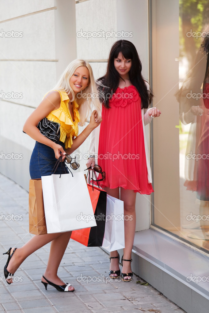 Two young women with shopping bags against a shop windows — Stock Photo #6858620