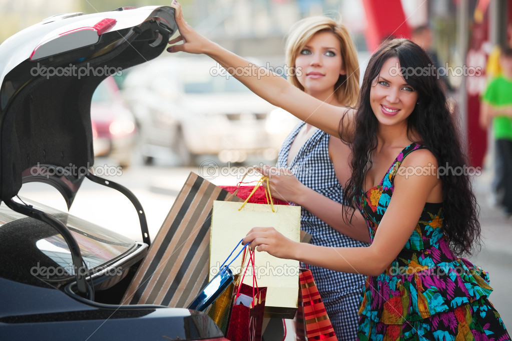Two young women loading a shopping bags in a car trunk — Lizenzfreies Foto #6858629