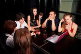 Young friends with laptop in a night bar — Stockfoto