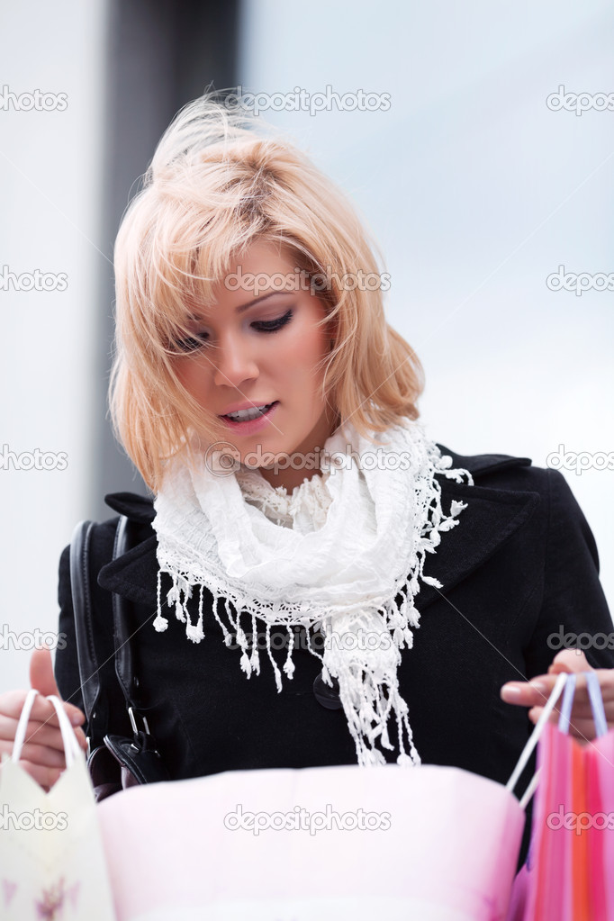 Young woman with shopping bags against a store window. — Stock Photo #6866276