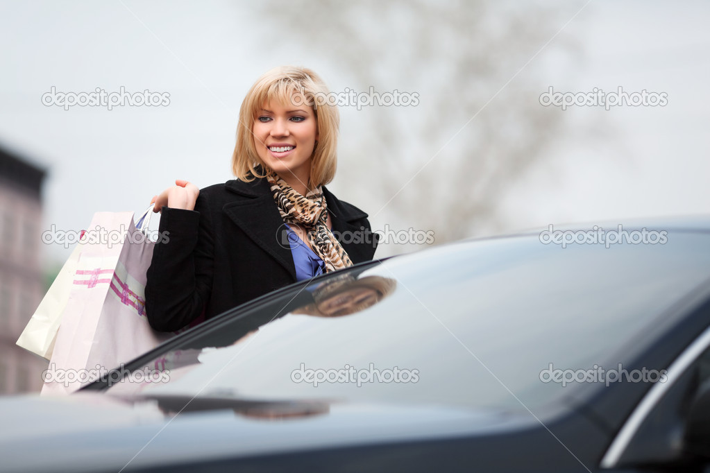 Young woman with shopping bags on a car parking — Stock Photo #6866299