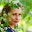 Beautiful woman among a spring blossom — Stock Photo