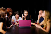 Young friends with laptop in a night bar — Stock Photo