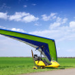 Stock Photo: Motorized hang glider over green grass