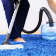 Vacuum cleaner in action-men cleaner a carpet. — Stock Photo