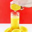 Stock Photo: Orange juice with hand, squeeze of orange.