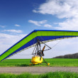 Motorized hang glider over green grass - Stock Photo