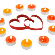 Two hearts, surrounded small candles. — Stock Photo