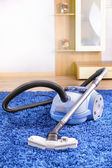 Vacuum cleaner stand on blue carpet. — Stock Photo