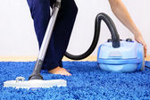 Vacuum cleaner in actie-mannen cleaner een tapijt. — Stockfoto