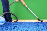 Odkurzacz w akcji mężczyźni czystsze dywan. — Zdjęcie stockowe