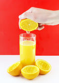 Orange juice with hand, squeeze of orange. — Stock Photo