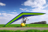 Motorized hang glider over green grass — Stok fotoğraf