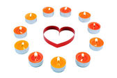 Single heart , surrounded small candles. — Stock Photo