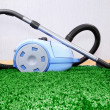 Vacuum cleaner on green carpet — Stock Photo