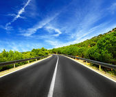 Asphalt road and blue sky with clouds — Stock Photo