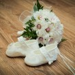 Shoes and bouquet on a wooden floor — Stock Photo #7175803